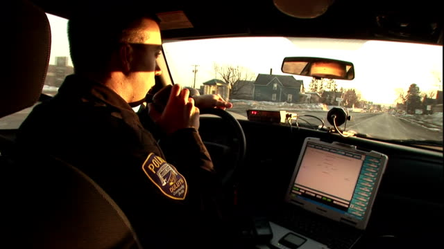a police officer talks into his radio as he drives his patrol car. - police force stock videos & royalty-free footage