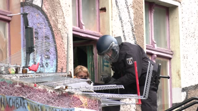 police officer tries to lead person out of liebigstrasse 34, also known as liebig34, during the eviction of its residents on october 09, 2020 in... - links platz stock-videos und b-roll-filmmaterial