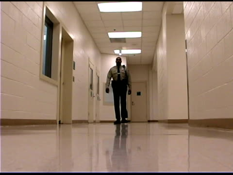 Police officer walking down corridor