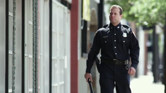 vídeos de stock e filmes b-roll de ms pan td police officer walking down sidewalk / dallas, texas, usa - maça