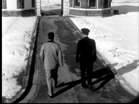 1956 ws police officer walking freed man out of kansas state penitentiary/ freed prisoner passing through old fashioned prison watch tower with prison guard on top/ lansing, kansas - leaving prison stock videos & royalty-free footage