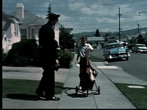 1965 ws pan police officer walking on suburban sidewalk and stopping paperboy/ boy and officer pointing finger in same direction/ ms officer taking notes as boy points and talks/ oakland, california/ audio - oakland california stock videos & royalty-free footage