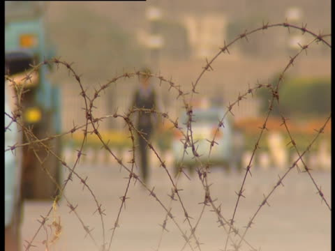 police officer walks behind wired fence in a street of islamabad - l'uomo e la macchina video stock e b–roll