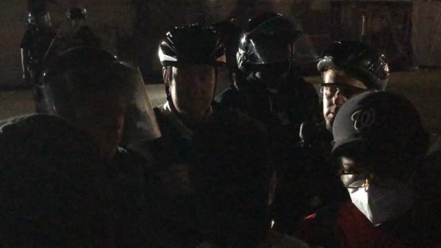 police officer wearing a cycling helmet behind a police shield discusses the situation of racism with the protester as police hold a perimeter as... - the march of time stock videos & royalty-free footage