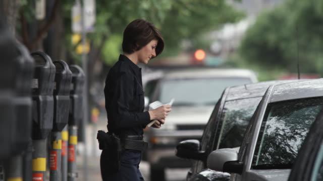 ms pan police officer writing parking tickets / dallas, texas, usa - justizwesen stock-videos und b-roll-filmmaterial