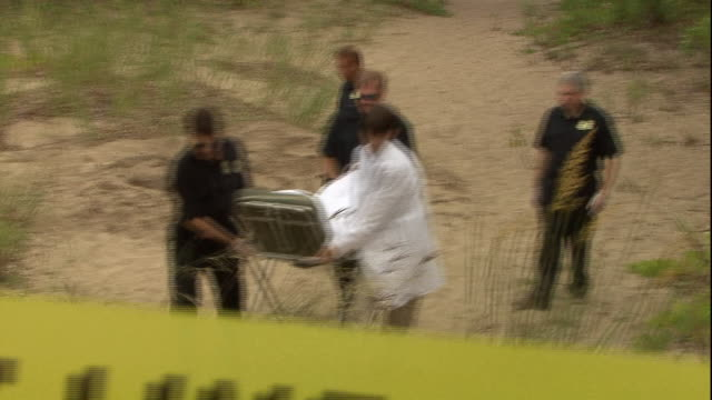 police officers and a coroner transport a dead body from a crime scene on a beach. - dead person stock videos & royalty-free footage
