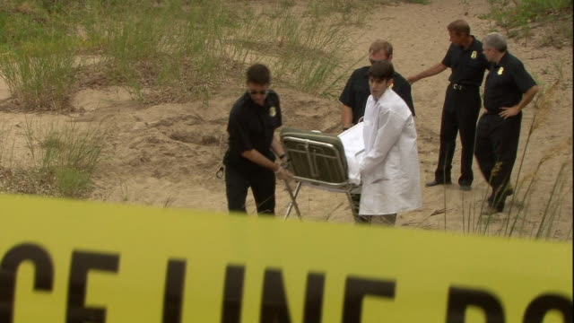 police officers and a coroner transport a dead body from a crime scene on a beach. - cadavere video stock e b–roll