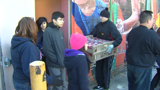 police officers and church members put together bags of food so that others can have meals on thanksgiving people unloading food donations from truck... - donation box stock videos & royalty-free footage