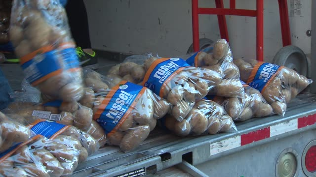 police officers and church members put together bags of food so that others can have meals on thanksgiving people unloading russet potatoes for... - donation box stock videos & royalty-free footage