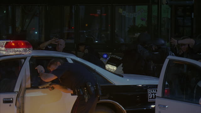 vidéos et rushes de police officers and members of a swat team ducking behind patrol cars and running away. - cache