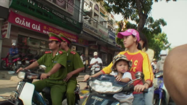 ms pov police officers and mothers with babies riding scooters, saigon, vietnam - motor scooter stock videos & royalty-free footage