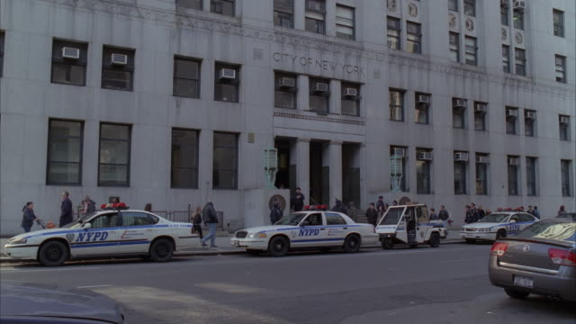 police officers and pedestrians walk past the new york city police department in new york city. - government building stock videos and b-roll footage