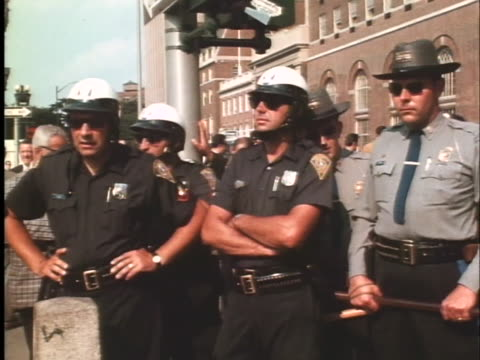 police officers and state troopers stand on the street in new haven, connecticut, as a demonstration is held in support of black panthers bobby seale... - ニューヘイブン点の映像素材/bロール