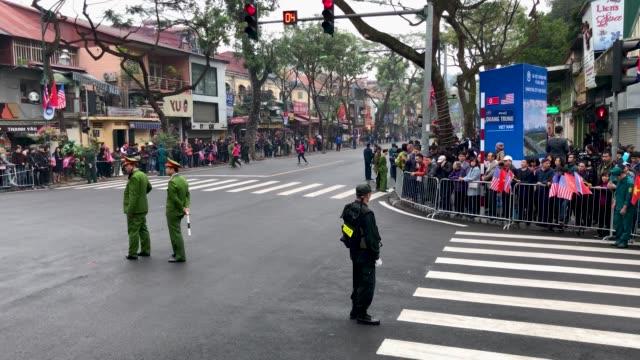 police officers block the road leading to the hotel metropole hanoi where us president donald trump and north korean leader kim jongun will later... - 首脳会議点の映像素材/bロール
