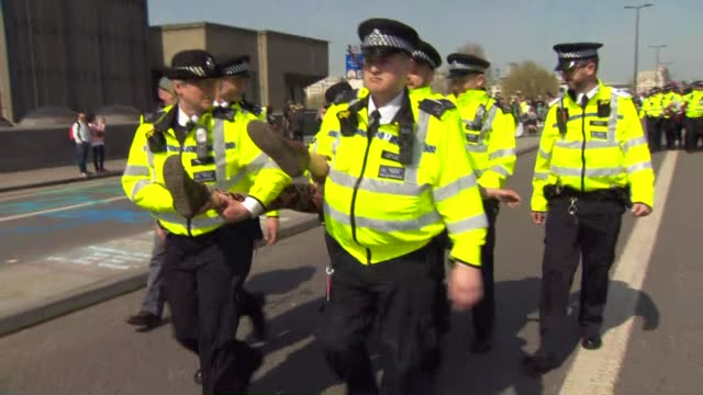 Police officers carry Extinction Rebellion climate change protestors off of Waterloo Bridge