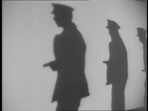 police officers carrying guns cast shadows on a wall - stjäla brott bildbanksvideor och videomaterial från bakom kulisserna