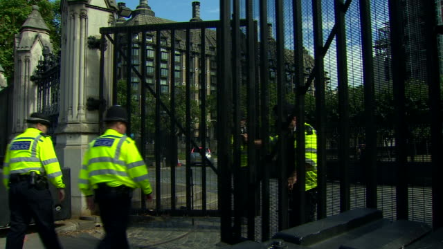 police officers closing the gates to the houses of parliament - defending stock videos & royalty-free footage