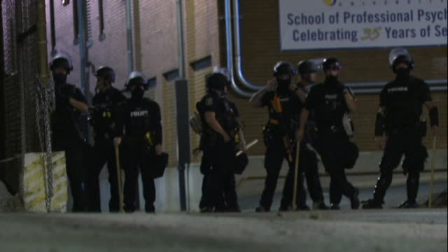 stockvideo's en b-roll-footage met police officers enforce louisville's curfew that went into effect at 9:00 pm. protesters hide in a nearby building, while officers block off exit... - clean