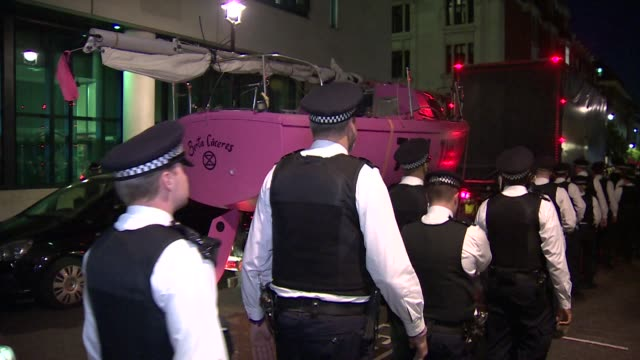 Police officers escort Extinction Rebellion climate change pink protest boat away from Oxford Circus