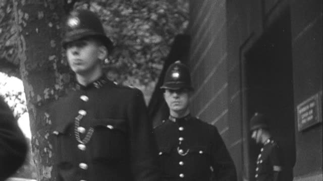 1939 MONTAGE Police officers exiting building in a row and firefighters running towards a fire station / United Kingdom