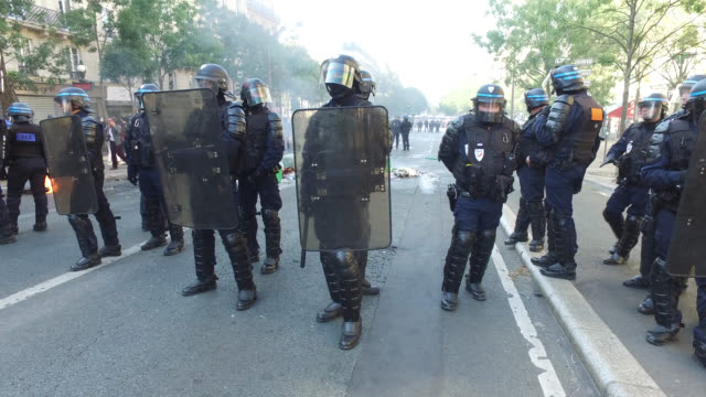 police officers gather next to burning rubbish bins during a climate change protest in paris on september 21, 2019. gobelins avenue. 75013 paris - french culture stock videos & royalty-free footage