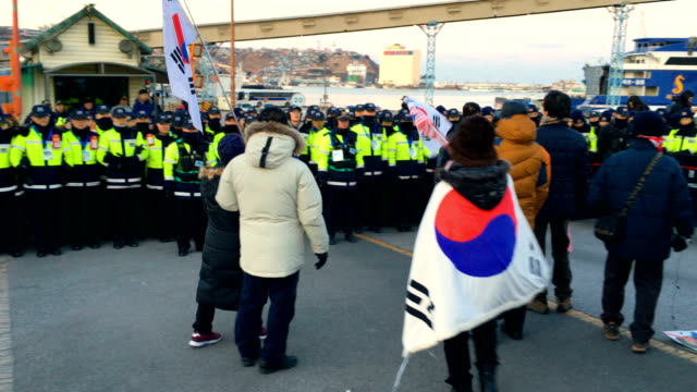police officers guard the entrance to the port during antinorth korea protests against the arrival of north korean ferry carrying north korea's... - südkorea stock-videos und b-roll-filmmaterial