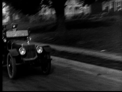 ms, b&w, police officers in car, driving fast through city, 1920's  - verfolgung stock-videos und b-roll-filmmaterial