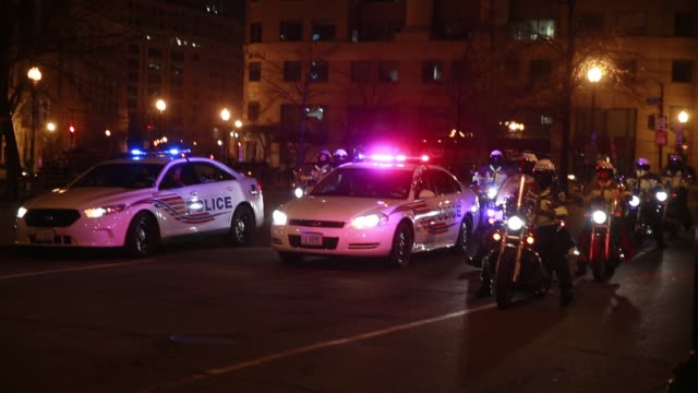 police officers in cars on bikes and on motorcycles rush past the intersection of 10th and new york in washington dc during protests against donald... - einsatzsirene stock-videos und b-roll-filmmaterial