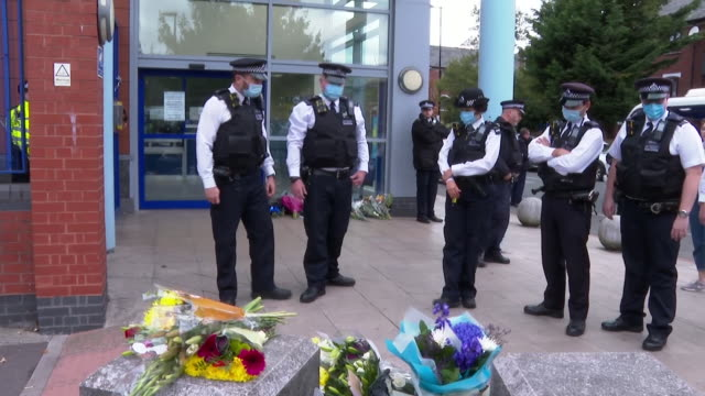 police officers laying flowers at a custody centre in croydon where sergeant matiu ratana was shot dead - crime and murder stock videos & royalty-free footage