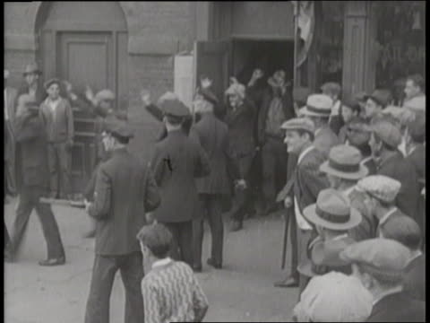 vídeos de stock e filmes b-roll de police officers lead a line of men out of a speakeasy and into paddy wagons - bar clandestino