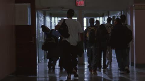 vídeos y material grabado en eventos de stock de police officers leaving a german shepherd in the hallway of a school after students go to class. - pasillo característica de edificio