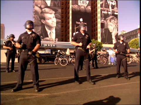 vídeos de stock e filmes b-roll de police officers lined up on street outside protests protesters against police brutality in los angeles - los angeles police department