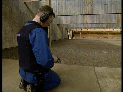 police officers load bullets into guns then take position to shoot at targets in firing range uk; 1994 - munition stock-videos und b-roll-filmmaterial