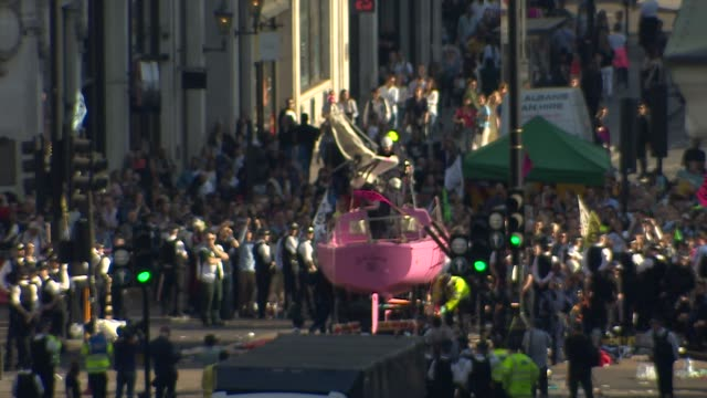 Police officers lower the mast and start the work to remove the Extinction Rebellion climate change pink protest boat from Oxford Circus