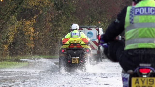 police officers on a quad bike and a motorbike drive through flood water at the worst affected village in south yorkshire - village stock videos & royalty-free footage