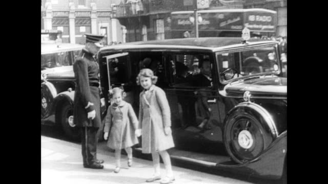 stockvideo's en b-roll-footage met / police officers outside of number 10 downing street, the residence of the british prime minster / daughters of george vi, margaret and elizabeth,... - 1936