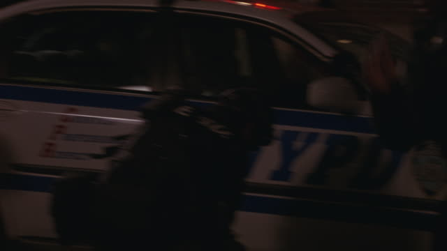 vidéos et rushes de police officers pushing a reporter and a photographer away as a swat team arrives at a crime scene. - pushing
