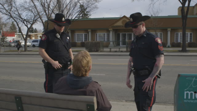 police officers question man drinking on bench of bus stop - canada stock videos & royalty-free footage