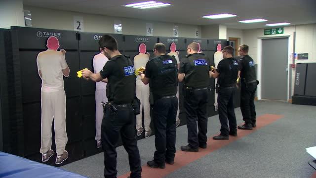 police officers receiving taser training in kent - waffe stock-videos und b-roll-filmmaterial