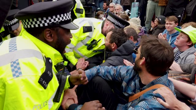 police officers remove protesters from a blockade on waterloo bridge during the second day of a coordinated protest by the extinction rebellion group... - ランベス点の映像素材/bロール