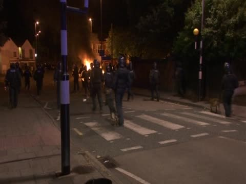 police officers run along a street where a car is burning on a riot night in birmingham august 2011 - burning stock-videos und b-roll-filmmaterial