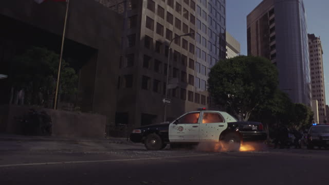 police officers shoot at the front of a high-rise as a car explodes on the street behind them. - police car stock videos & royalty-free footage