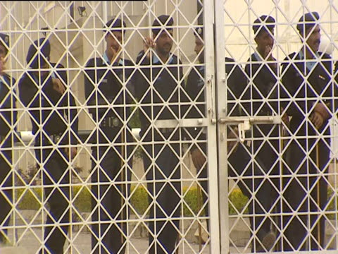 police officers stand behind a wired fence - l'uomo e la macchina video stock e b–roll