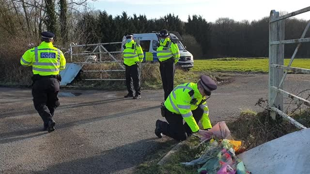 vídeos de stock e filmes b-roll de police officers stand by flowers brought by members of the public to the entrance of great chart golf and leisure in ashford in kent, after... - encontrar