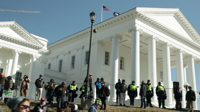 police officers stand guard during a rally organized by the virginia citizens defense league on capitol square near the state capital building... - virginia us state stock videos & royalty-free footage