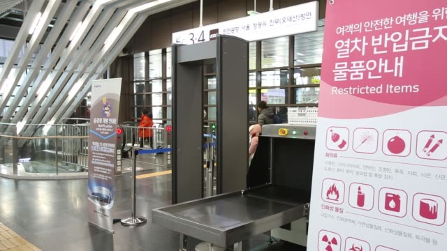 police officers stand next to a metal detector and luggage scanner at gangneung station ahead of the 2018 pyeongchang winter olympic games in... - 韓国点の映像素材/bロール