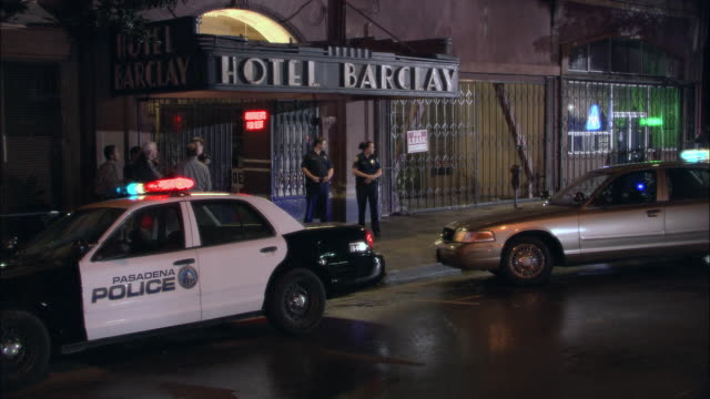 HA Police officers standing outside Hotel Barclay on a rainy night with emergency lights flashing on police cars and bystanders watching / Pasadena, California, United States