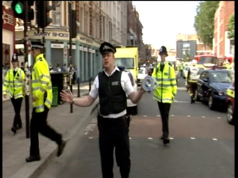 vídeos y material grabado en eventos de stock de police officers walk down street waving people away from scene of attempted bomb attack on bus hackney 21 jul 05 - estilo del 2000