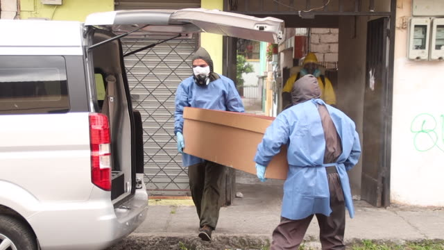 police officers wear biosecurity suits while carrying cardboard coffin that contains possible covid victim. - spray stock videos & royalty-free footage