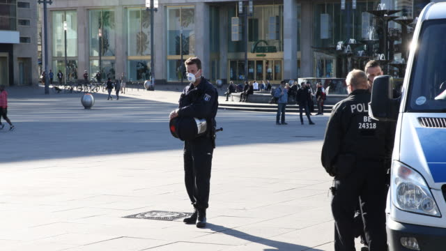 police officers wearing protective face mask and patrol at alexanderplatz to make sure people are not gathering in too-large groups during the novel... - polizei stock-videos und b-roll-filmmaterial